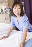 Una enfermera que hace una sonrisa de la cama Fotos de archivo libres de regalías