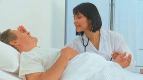 Una enfermera que usa un estetoscopio en su paciente almacen de video