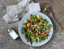 Una ensalada vegetal vegetariana en una placa gris en una tabla de madera Foto de archivo