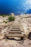 Una escalera de madera lleva abajo al río Fotos de archivo libres de regalías