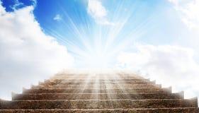 Una escalera de piedra de la manera hasta el cielo azul, hay una luz fuerte en el final de la manera Foto de archivo libre de regalías
