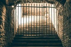 Una escalera desalentadora que lleva a un paso bloqueado por una rejilla del hierro en una mazmorra medieval imagen de archivo