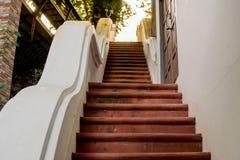 Una escalera en un monasterio, con un piso y una luz del sol parduscos imagenes de archivo