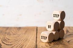 Una escalera simbolizada por los cubos y el lema: paso a paso fotos de archivo
