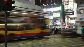 Una escena ocupada de la calle de la noche por completo de la gente y de móviles metrajes