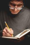 Una escritura mayor del hombre en un cuaderno fotografía de archivo