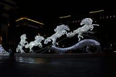 Una escultura que brilla intensamente de la Navidad en la forma de cuatro caballos en la calle por la tarde Imágenes de archivo libres de regalías