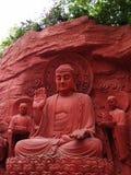 Una escultura roja de Buddha con los criados Fotos de archivo libres de regalías
