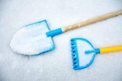 Una espada y un rastrillo del juguete del ` s del niño se fueron afuera en la nieve Imágenes de archivo libres de regalías
