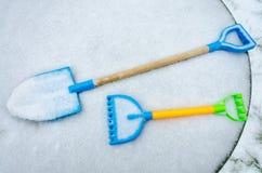 Una espada y un rastrillo del juguete del ` s del niño se fueron afuera en la nieve Foto de archivo libre de regalías