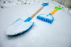 Una espada y un rastrillo del juguete del ` s del niño se fueron afuera en la nieve Imagen de archivo libre de regalías