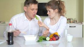 Una esposa y un marido se está sentando en una tabla que comen los tallarines chinos y las verduras frescas El concepto de nutric almacen de video