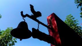 Una esquina de la pared con una estatua y una ejecución de la campana en las sombras, diciendo el tiempo por la mañana fotografía de archivo