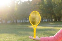 Una estafa de tenis en su mano coge la bola en el movimiento Imagen de archivo