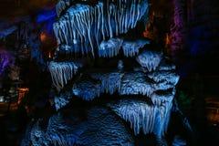 Una estalactita y una estalagmita excavan en color azul Foto de archivo libre de regalías