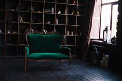 Una estantería enorme para los libros y el sofá del vintage Foto de archivo