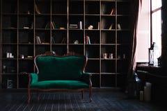 Una estantería enorme para los libros y el sofá del vintage Imagen de archivo libre de regalías