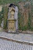 Una estatua con un hombre que lleva a cabo una escultura de Jesús crucificado en su mano Imagenes de archivo