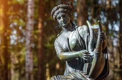 Una estatua de cobre femenina de una deidad con una arpa en el bosque Foto de archivo