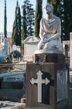 Una estatua de la mujer en sus rodillas ruega para dios sobre la piedra sepulcral Imagen de archivo libre de regalías