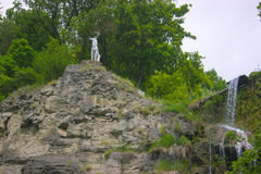 Una estatua de los ciervos cerca de la cascada fotografía de archivo libre de regalías