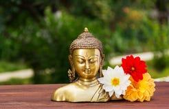 Una estatua de oro de Buda en un jardín soleado del verano Aster de Buda y de las flores Relájese y meditación Copie el espacio Foto de archivo