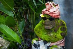 Una estatua de piedra de un mono con los vidrios Imagenes de archivo