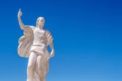 Una estatua de St Elías el profeta que sostiene un cuchillo en un cielo azul Foto de archivo