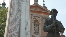Una estatua del soldado cerca de un monumento de guerra bendecido por una estatua del santo en Italia metrajes
