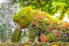 Una estatua grande del cerdo de la sentada y de la sonrisa adornada con las flores hermosas y las flores coloridas en un parque e fotografía de archivo