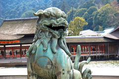 Una estatua protege la entrada a un templo en Japón foto de archivo