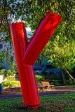 Una estatua roja que parece la letra y imagen de archivo