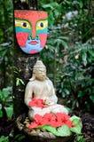 Una estatua y una máscara de buddha Imagen de archivo