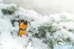 Una estatuilla de perros en una rama de árbol Símbolo del año 2018 Imagenes de archivo