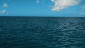 Una estela de una nave en el mar con agua azul del océano, un horizonte, el cielo azul y las nubes metrajes