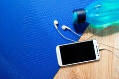 Una estera para las clases de la yoga y de los pilates, un teléfono con los auriculares y una botella de agua en el piso de mader imagen de archivo libre de regalías