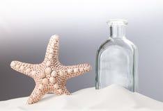 Una estrella de mar y una botella vacía en la arena blanca Primer Espacio de la copia del concepto Imagen de archivo
