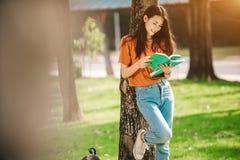 Una estudiante asiática joven o adolescente en universidad que sonríe y que lee el abucheo Imagenes de archivo