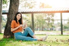 Una estudiante asiática joven o adolescente en universidad que sonríe y que lee el libro y la mirada en la tableta Foto de archivo libre de regalías