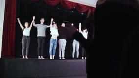 Una etapa del teatro Paseos de los actores de la gente hacia la audiencia y los arcos que llevan a cabo las manos metrajes