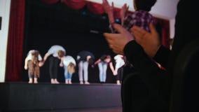 Una etapa del teatro Paseos de los actores de la gente hacia la audiencia y los arcos que llevan a cabo las manos La audiencia qu almacen de metraje de vídeo