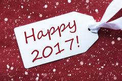 Una etiqueta en el fondo rojo, copos de nieve, manda un SMS a 2017 feliz Imagen de archivo libre de regalías