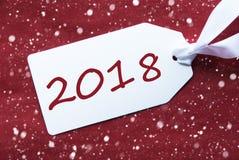 Una etiqueta en el fondo rojo, copos de nieve, texto 2018 Foto de archivo