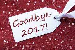 Una etiqueta en el fondo rojo, copos de nieve, texto adiós 2017 Fotografía de archivo