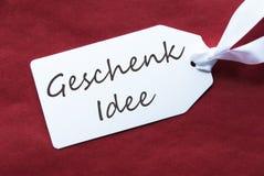 Una etiqueta en el fondo rojo, Geschenk Idee significa idea del regalo Foto de archivo libre de regalías