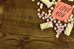 Una etiqueta engomada con el texto: TE AMO adornado con los dulces de la melcocha Concepto del amor en fondo de madera Imagen de archivo