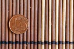 Una euro bugia della moneta sulla denominazione di bambù di legno della tavola è di 1 euro centesimo Immagine Stock