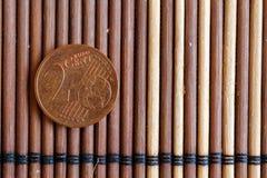 Una euro bugia della moneta sulla denominazione di bambù di legno della tavola è euro centesimo 2 Fotografia Stock Libera da Diritti