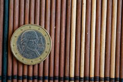 Una euro bugia della moneta sulla denominazione di bambù di legno della tavola è 2 euro - lato posteriore fotografia stock