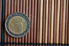 Una euro bugia della moneta sulla denominazione di bambù di legno della tavola è 2 euro - lato posteriore immagini stock libere da diritti